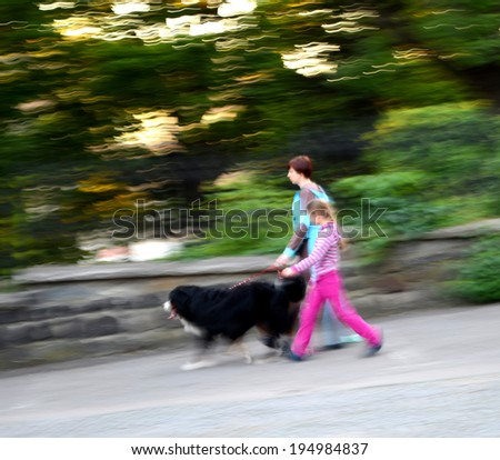 Mother and daughter walking with a dog in motion blur - stock photo