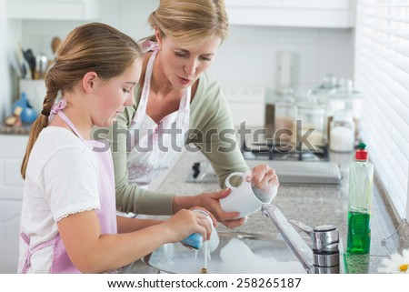 Mother and daughter washing up together at home in the kitchen - stock photo