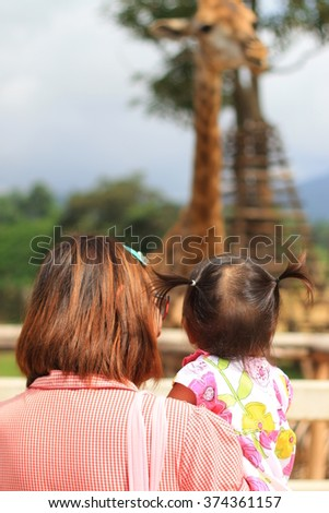 Mother and daughter watching the giraffes at zoo - stock photo