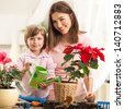 Mother and daughter watering plants together. - stock photo