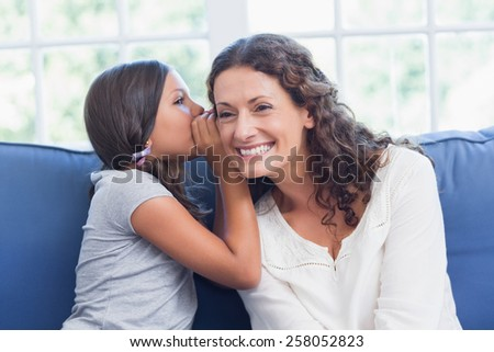 Mother and daughter whispering in the living room - stock photo