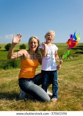 Mother and daughter with a pinwheel outdoors - stock photo
