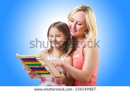 Mother and daughter with abacus on white - stock photo