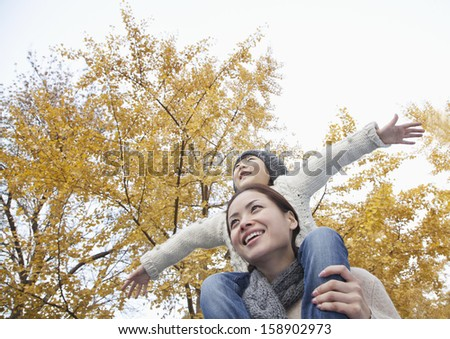 Mother and daughter with arms outstretched and surrounded by autumn trees - stock photo