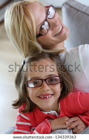 Mother and daughter with eyeglasses on - stock photo