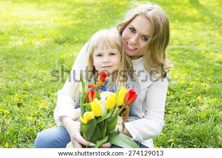 Mother and daughter with flowers playing in spring park. Mothers day celebration concept - stock photo