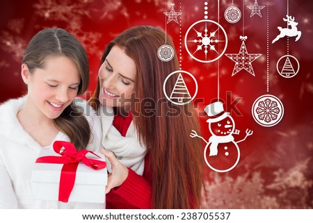 Mother and daughter with gift against red snow flake pattern design - stock photo