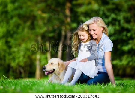 Mother and daughter with labrador sitting on the green grass at the summer park - stock photo