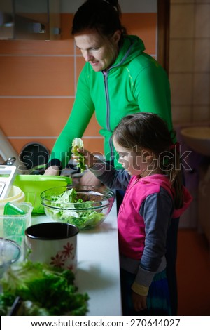 Mother and daughter working together, washing salad and preparing meal for the family in a messy kitchenette. Authentic situation of a child doing chores in the household, domestic help concept.  - stock photo