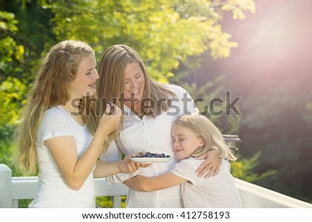 Mother and daughters enjoying the summer day on outdoor deck while eating fresh blue berries. Light haze effect applied to image. 