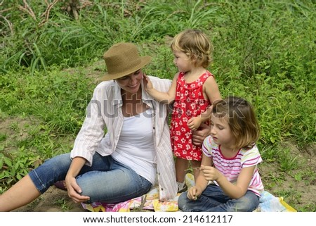 Mother and daughters playing outdoors in nature - stock photo