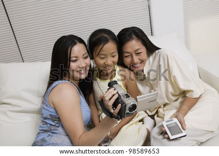 Mother and Daughters with Video Camera and PDA - stock photo
