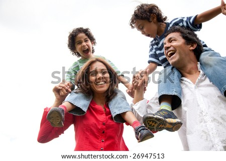 mother and father carrying their sons on their shoulders - stock photo