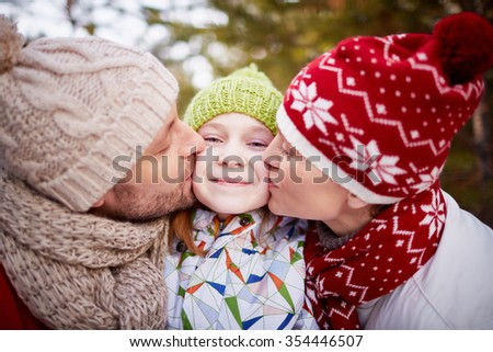 Mother and father giving a kiss to their daughter outdoors - stock photo