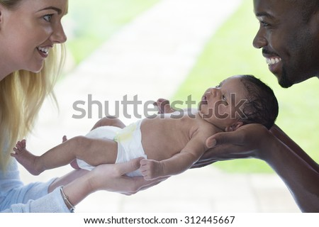 Mother and Father holding their newborn baby. They are looking at each other and smiling. - stock photo