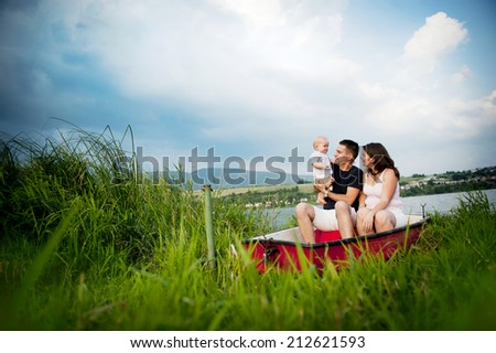 Mother and father with baby boy on boat on lake - stock photo