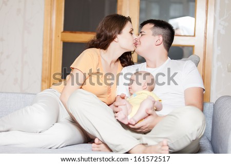 mother and father with their baby on the couch at home - stock photo
