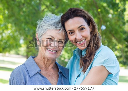 mother and grandmother smilling in a park on a sunny day - stock photo