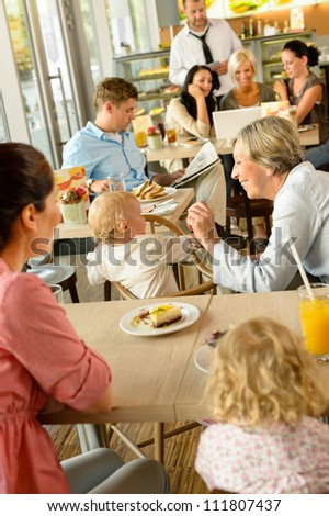 Mother and grandmother with children at cafe eating cake women - stock photo