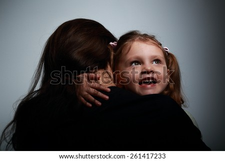 Mother and happy smiling daughter hugging on dark background - stock photo
