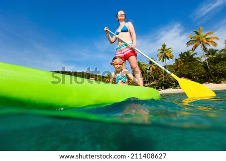 Mother and her adorable little daughter paddling on stand up board having fun during summer beach vacation - stock photo