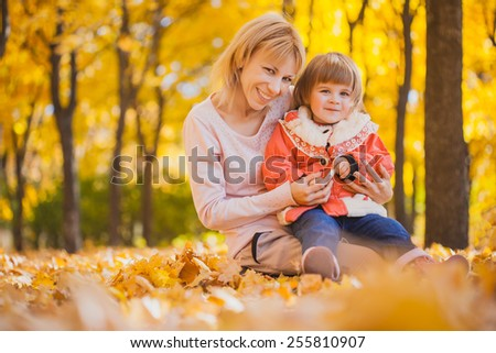 mother and her baby have fun in the autumn park - stock photo