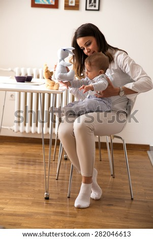 Mother and her baby playing with toys. - stock photo