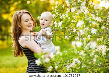 Mother and her child in spring park - stock photo