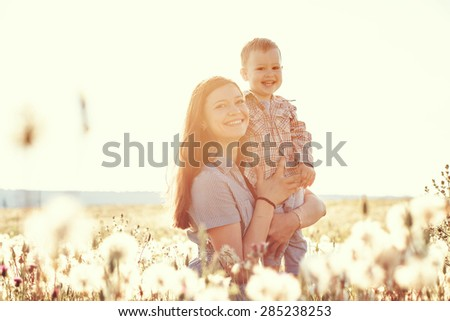 Mother and her child playing in spring field in soft sunlight - stock photo