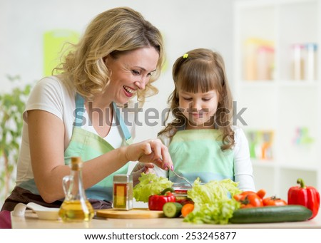 mother and her child preparing and tasting healthy food - stock photo