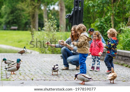Mother and her children feeding ducks at summer, two little boys and adorable girl - stock photo