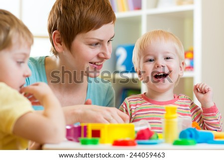 mother and her children have fun with colorful play clay toys - stock photo