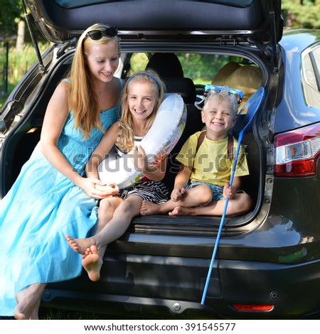 mother and her children sits in car - stock photo