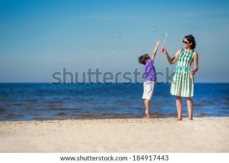 Mother and her cute little son enjoying time at tropical beach - stock photo