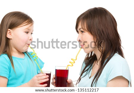 Mother and her daughter are drinking juice using straws, isolated over white - stock photo