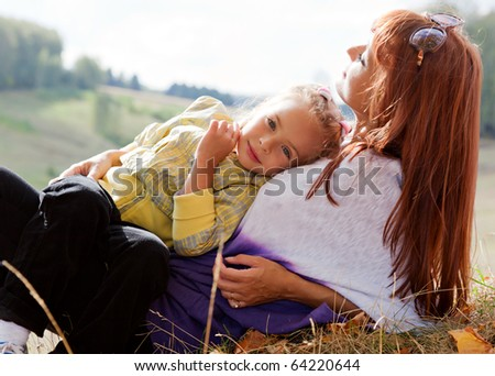 Mother and her daughter are in autumn park - stock photo