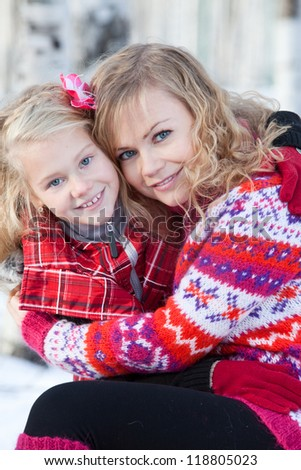 Mother and her daughter are sitting close each other in park in winter. They are happy and are smiling. - stock photo
