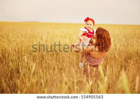 mother and her daughter at the wheat field - stock photo