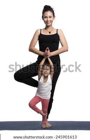 Mother and her daughter doing yoga exercise on studio white background. - stock photo
