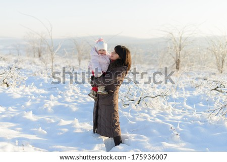 mother and her daughter standing in snow - stock photo