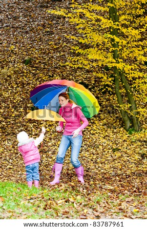 mother and her daughter with umbrellas in autumnal nature - stock photo