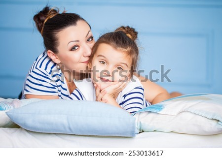 Mother and her happy daughter lying on a bed - stock photo
