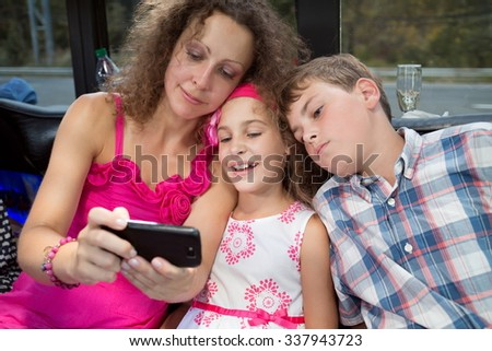Mother and her kids are watching a movie in phone. - stock photo