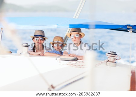 Mother and her kids having great time sailing at luxury yacht or catamaran boat - stock photo