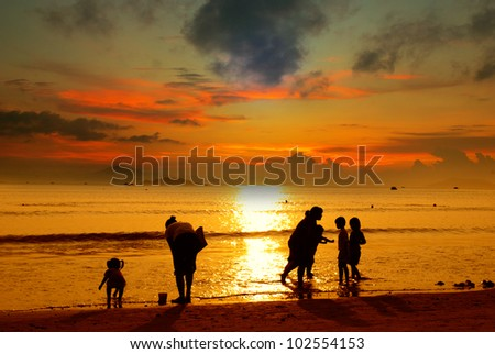 Mother and her kids silhouettes on beach at sunset - stock photo