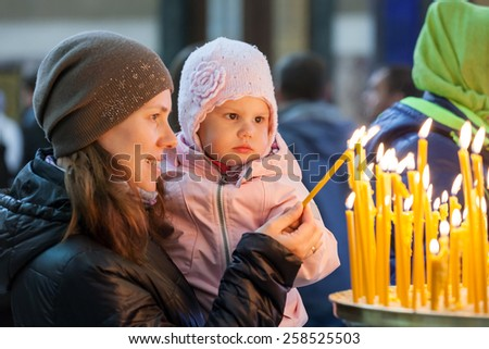 Mother and her little blond Caucasian daughter in Orthodox Russian Church - stock photo