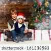 Mother and her lIttle boy in Santa hat with gift box under christmas tree in wooden house interior  - stock photo