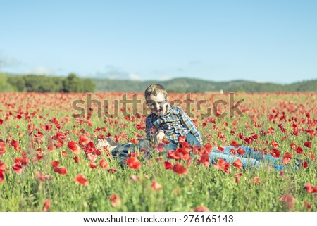 Mother and her little child having fun in a field, flower in foreground - stock photo