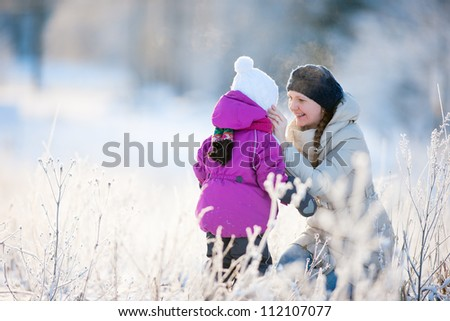Mother and her little daughter enjoying beautiful winter day outdoors - stock photo