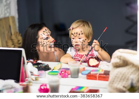 Mother and her little daughter painting their faces in front of the mirror - stock photo